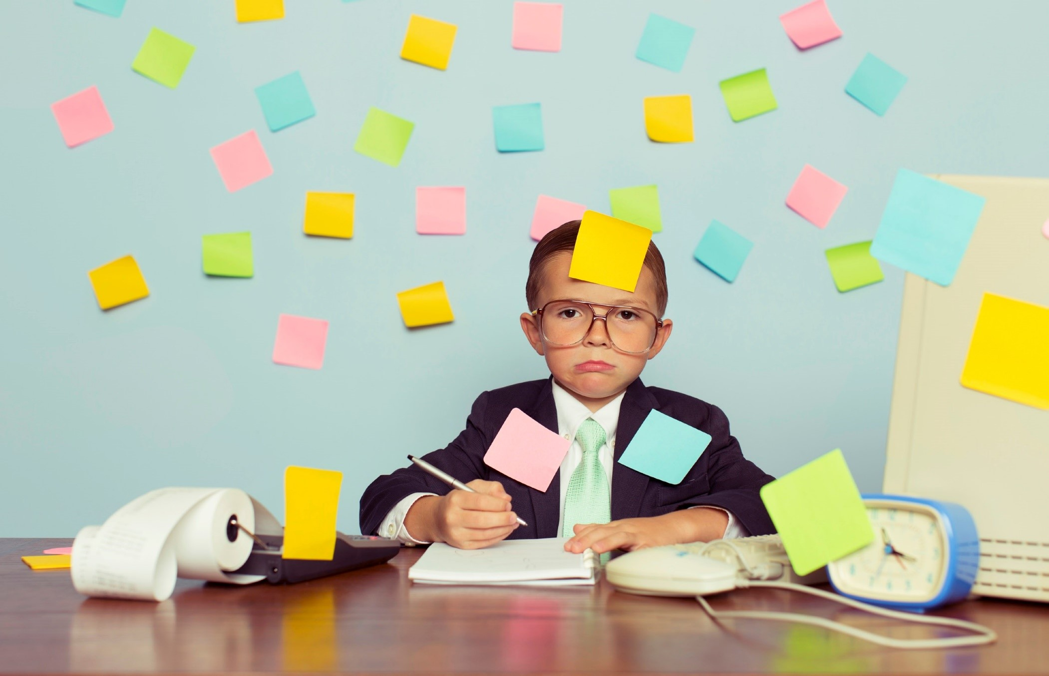 Child at desk covered in post-it notes